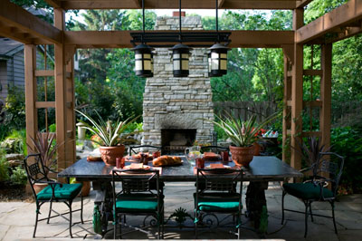 An outdoor dining room under a wooden pergola