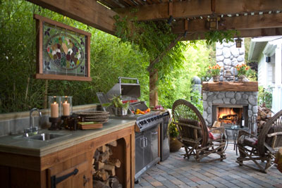 A covered outdoor kitchen with a fireplace