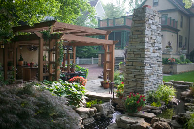 A lush backyard with a stream and pergola