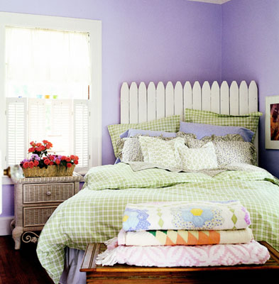 A summer style room with purple walls and a white picket fence headboard