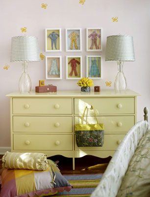 A yellow dresser with boll dress-up clothes in frames above it