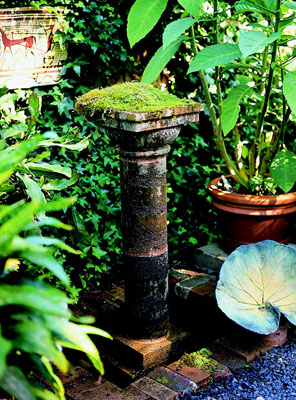 A moss covered pillar surrounded by plants