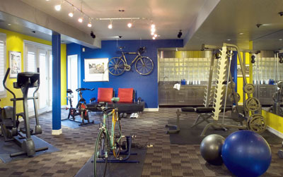 A workout room complete with weights, stationary bikes, and an eliptical