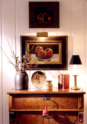 A cabinet with several books, a plant, a plate, and a lamp on it