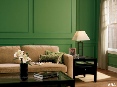 A living room couch with a forrest green painted wall