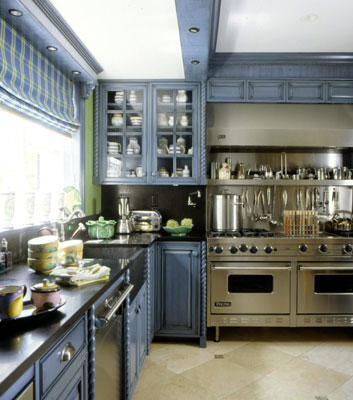A modern kitchen with dark cabinets and a stainless steel stove and oven