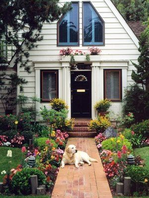 A brick walkway to the front door of a house with a dog laying on the walkway