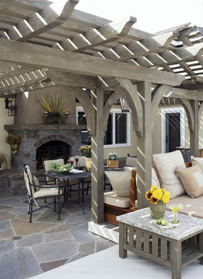 Outdoor furniture under a pergola with a built-in fireplace