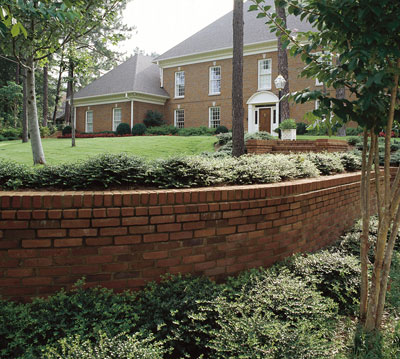 A brick and mortar retaining wall surrounded by plants