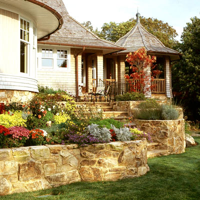 Flower beds in a retaining wall with stairs leading to the back door of a house